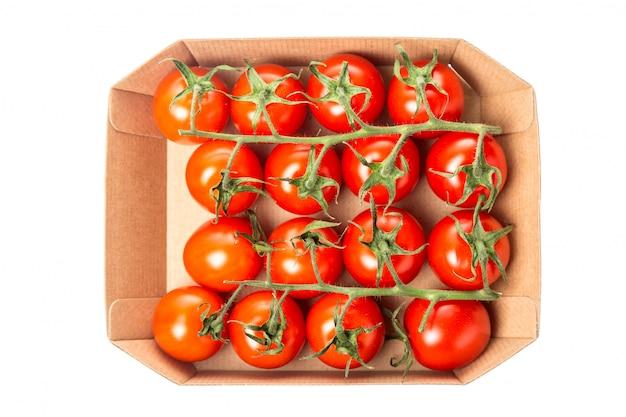Pomodori ciliegia rossi succosi freschi in una scatola isolata. vista dall'alto.