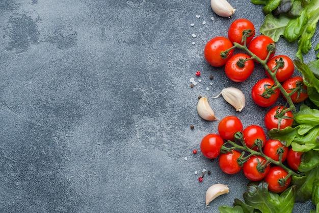Pomodori ciliegia su un ramo erbe fresche e spicchio d'aglio con spezie su un tavolo di pietra scura.