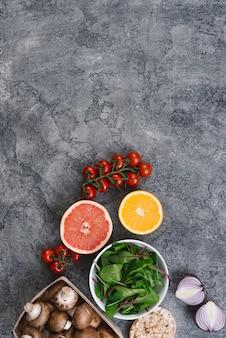 Pomodori ciliegini; agrumi dimezzati; spinaci; funghi; torta soffiata di cipolle e riso su fondale in cemento