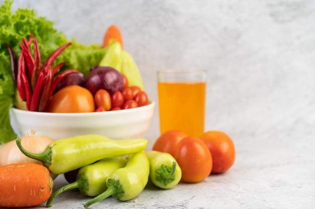Pomodori, cipolle rosse, peperoni, carote e cavolo cinese in una tazza bianca sul pavimento di cemento.