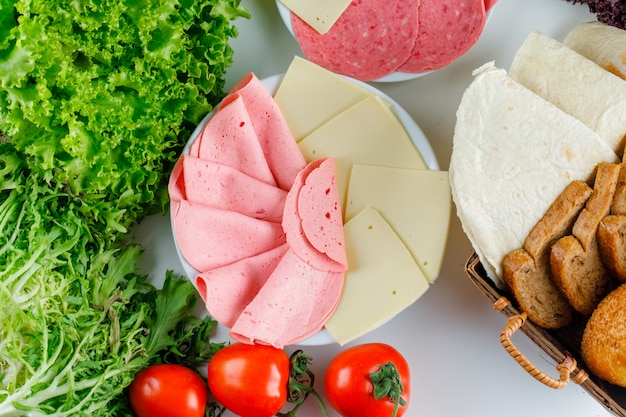 Pomodori con verdure a foglia verde, pane, formaggio, salsiccia piatta