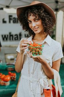 Pomodori d'acquisto della bella donna ad un mercato degli agricoltori