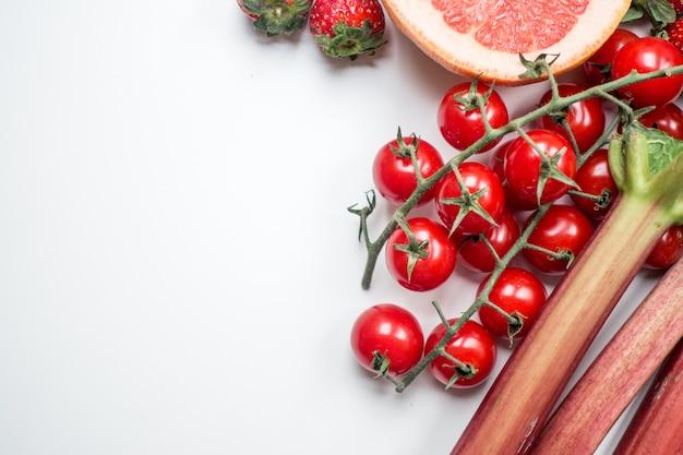 Pomodori di ciliegia rossi e rabarbaro su una priorità bassa bianca