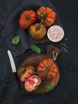 Pomodori di hairloom maturi freschi e foglie del basilico sul bordo di legno rustico sopra la tavola di pietra nera