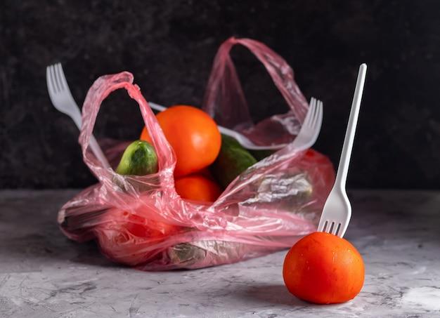 Pomodori e cetrioli in un sacchetto di plastica su uno sfondo scuro