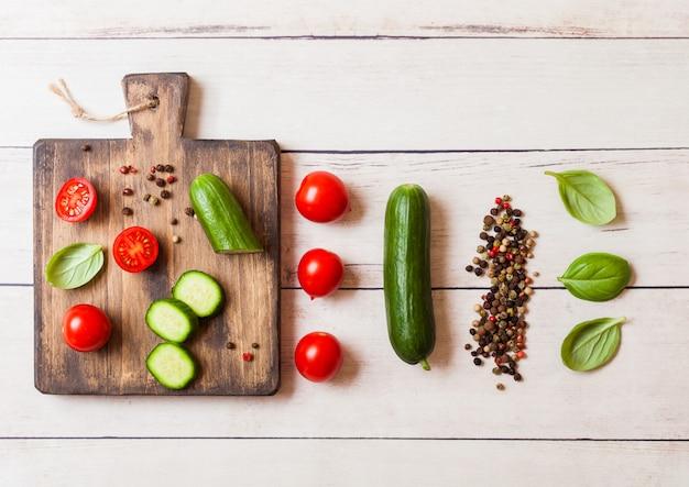 Pomodori e cetrioli organici con basilico e asciugamano di tela sul tagliere sul tavolo da cucina di legno.