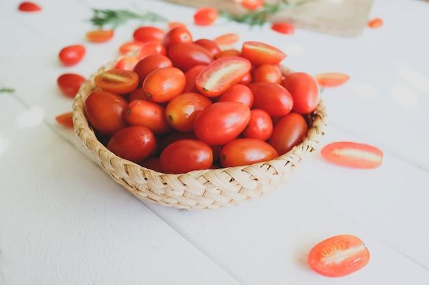 Pomodori e rosmarino freschi su una priorità bassa bianca.