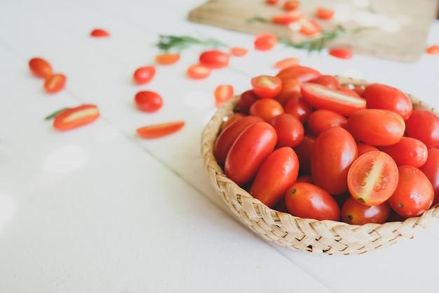 Pomodori freschi e rosmarino su bianco.