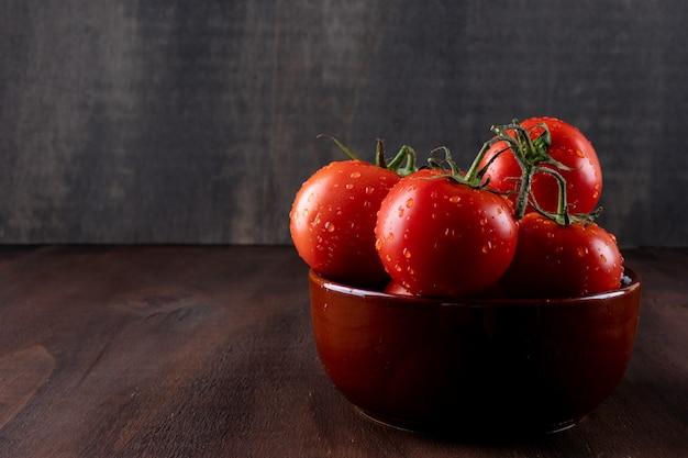 Pomodori freschi e sani in ciotola ceramica sulla superficie marrone della pietra
