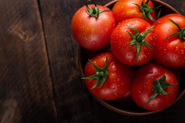Pomodori freschi in un piatto su oscurità. raccolta pomodori.