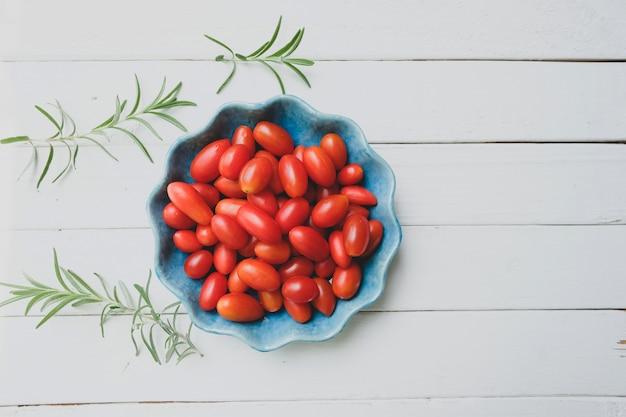 Pomodori freschi in una ciotola blu e rosmarini su bianco. vista dall'alto.