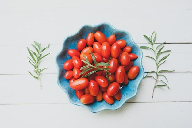 Pomodori freschi in una ciotola blu e rosmarini su bianco