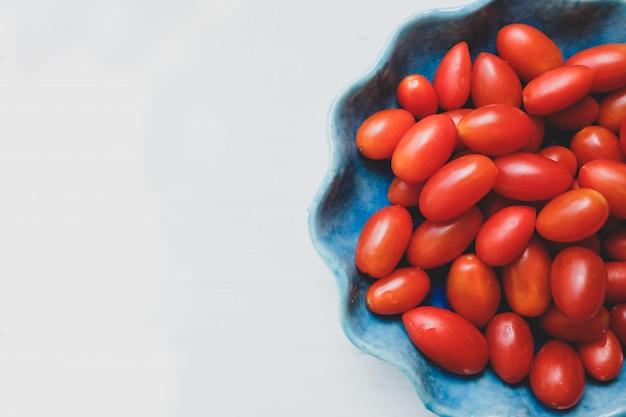Pomodori freschi in una ciotola blu su bianco. vista dall'alto.