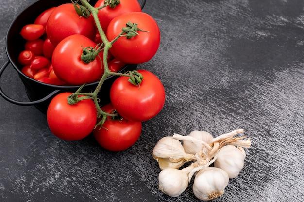 Pomodori freschi in una pentola e aglio