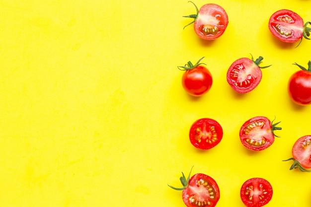 Pomodori freschi, interi e mezzo taglio isolati su giallo