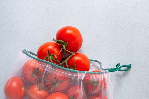 Pomodori in confezione ecologica. sacchetti riutilizzabili per verdure. imballaggio ecologico.