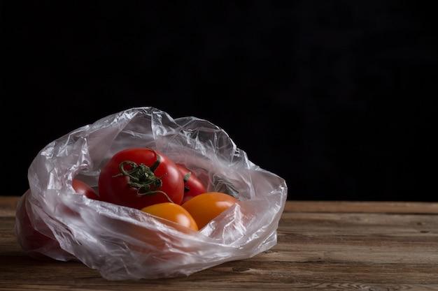 Pomodori in un sacchetto di plastica. l'immagine mostra gli effetti dannosi dei sacchetti di plastica sul cibo.