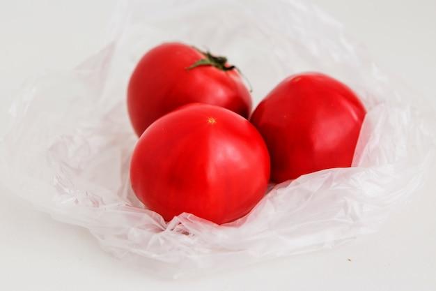 Pomodori in un sacchetto di plastica su uno sfondo chiaro