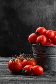 Pomodori in una vista laterale del mini secchio sulla parete di legno e scura grigia