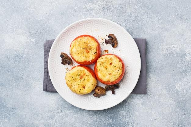 Pomodori interi al forno ripieni di funghi e formaggio con spezie. copia spazio.