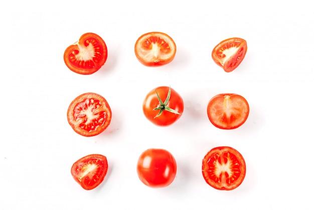 Pomodori interi e tagliati degli ortaggi freschi su isolamento bianco del fondo