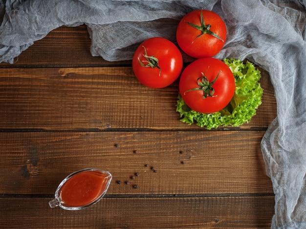 Pomodori, lattuga, salsa e condimento. vista dall'alto. il concetto di mangiare sano e vegetarismo.