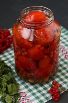 Pomodori marinati con un viburno in un barattolo aperto