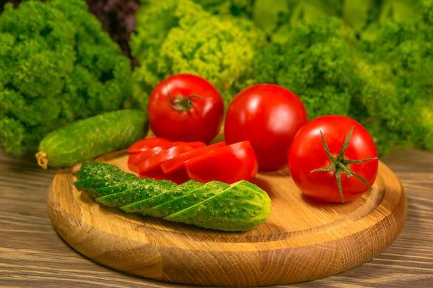 Pomodori maturi freschi su una tavola di legno con un'insalata verde