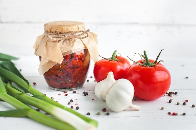 Pomodori nel barattolo. pomodori secchi fatti in casa. chiusura temporanea. cibo in scatola estivo e autunnale. conservare con spezie e verdure.