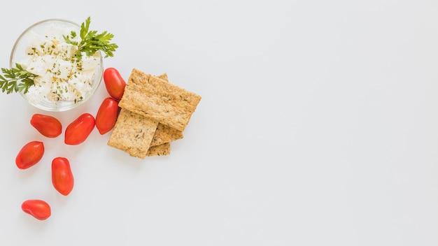 Pomodori rossi e pane croccante con ciotola di formaggio su priorità bassa bianca