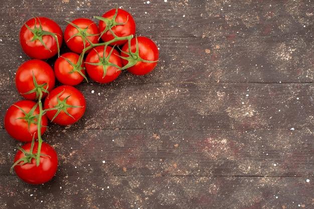 Pomodori rossi freschi di vista superiore maturi e interi su marrone di legno