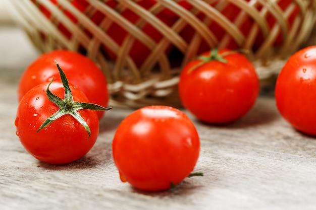 Pomodori rossi freschi in un cestino di vimini su una vecchia tabella di legno. pomodorini maturi e succosi con gocce di umidità, tavolo di legno grigio, intorno a un panno di tela. in stile rustico.