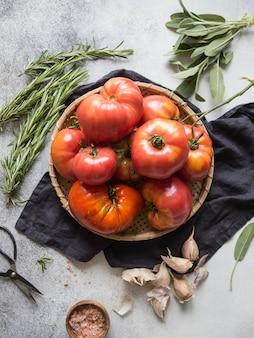 Pomodori rossi freschi su un piatto di vimini rotondo, sale rosa in una ciotola di legno, aglio.