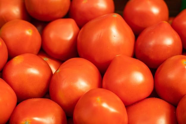 Pomodori rossi luminosi in primo piano.