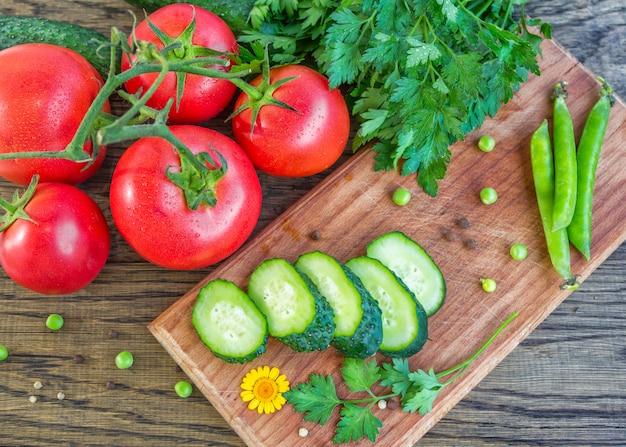 Pomodori rossi maturi, cetriolo affettato, mazzo di prezzemolo, piselli e pepe in grani sul tavolo.