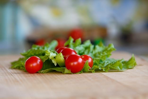 Pomodori rossi maturi su una tabella contro le foglie verdi di lattuga.