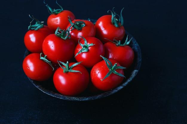 Pomodori rossi organici freschi in banda nera, fine su, concetto sano, vista superiore