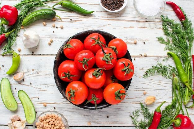 Pomodori rossi organici freschi in banda nera sul tavolo di legno bianco con verde e rosso e peperoncino, peperoni verdi, grani di pepe neri, sale, primi piani, concetto sano
