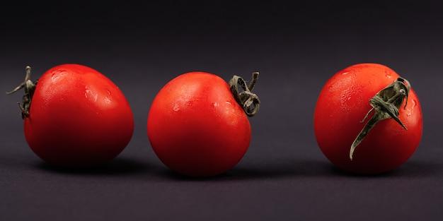 Pomodori rossi su un primo piano sfondo scuro, panorama.