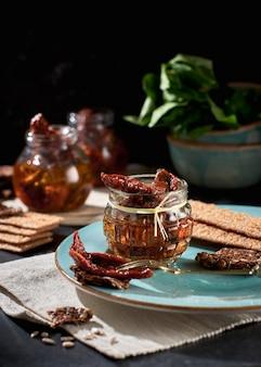 Pomodori secchi con olio d'oliva in un barattolo di pane di segale e una cappella