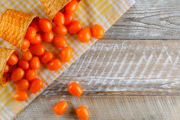 Pomodori sparsi da cestini di vimini piatti giacevano sul panno da picnic e tavolo in legno