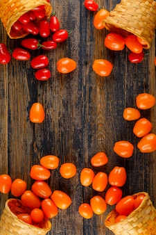 Pomodori sparsi dalla vista superiore dei canestri di vimini su una tavola di legno
