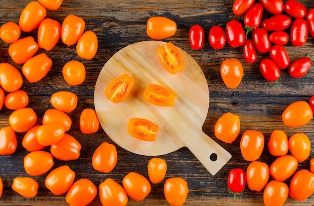 Pomodori sparsi sul tagliere di legno e. disteso.