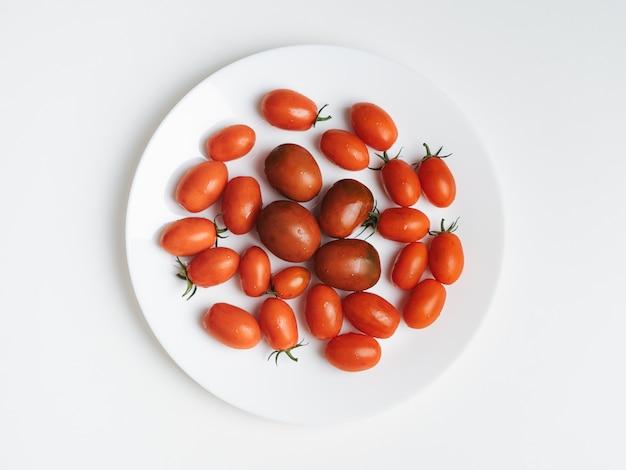 Pomodori su un piatto bianco. sfondo bianco. fotografia di cibo,