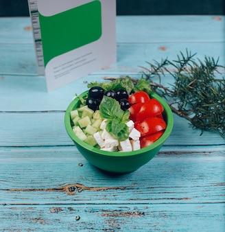 Pomodori tritati, formaggio bianco e olive nere nella ciotola verde.