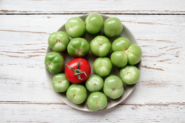 Pomodori verdi, sottaceti sul tavolo di legno bianco con verde e rosso e peperoncino, finocchio, sale, grani di pepe neri, aglio, pisello, da vicino, concetto sano, vista dall'alto, piatto