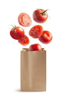 Pomodori volanti, sacchetto di carta riciclabile, isolato dallo sfondo bianco