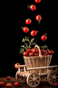 Pomodorini che cadono nel cesto. levitazione alimentare