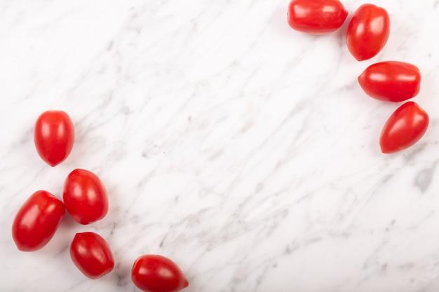 Pomodorini su uno sfondo di marmo bianco con spazio di copia