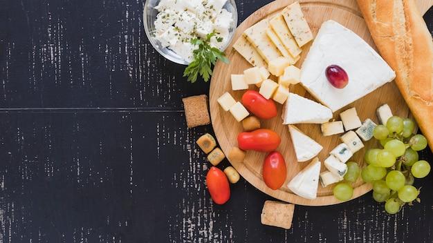 Pomodorini, uva, blocchi di formaggio e baguette sul tagliere rotondo sullo sfondo con texture